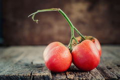 Composition from Red Tomatoes with drops on the wooden backgroun Stock Photo