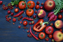 The composition of red vegetarian products: fruits and vegetables on wooden background. Apples, tomatoes, currants, radishes, pepp Royalty Free Stock Photography