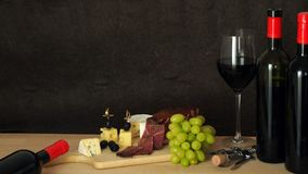 Composition of red wine with cheese, ham and grapes royalty free stock photos