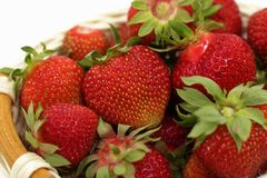 Composition of ripe strawberries on a white background in a wicker basket royalty free stock images
