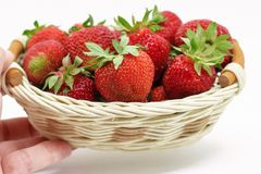 Composition of ripe strawberries on a white background in a wicker basket stock photos