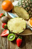 Tropical fruits. Pineapple, oranges, kiwi, strawberries. Fruit on a cutting board. Pineapple slice stock photography