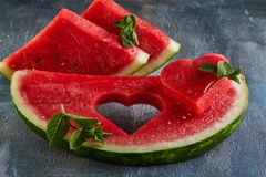 Composition with ripe watermelon, mint leaves and a heart carved in a slice of watermelon. Concept for valentines day stock image
