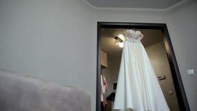 Composition - robe de mariage sur un mur bleu gris avec le décor et les accessoires banque de vidéos