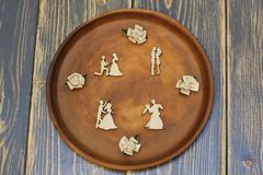 Composition of romantic meetings from vintage wooden figures and decorative flowers from satin on ceramic dish. Dark rough wooden. Romantic mood. Vintage figures royalty free stock images