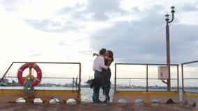 Composition romantique du couple étreignant et de baiser par le temps venteux sur le pilier banque de vidéos