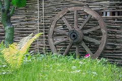 Composition of a rural landscape from a wicker fence and a wooden wheel on a summer day. Composition of a rural landscape from a wicker fence and a wooden wheel royalty free stock photography