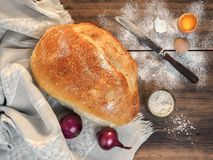 Composition in a rustic style, top view. Still life with bread on the background of the tablecloth and old wood. Scattered on the table flour, soup with salt Stock Images