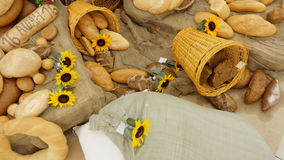 Composition of rye breads, bag  flour and baguettes with sunflowers on wooden table. Top  view. Royalty Free Stock Photos