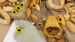 Composition of rye breads, bag  flour and baguettes with sunflowers on the wooden table. Top  view. Stock Photography