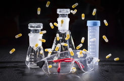 Composition: safety glasses, chemical glassware and capsules Stock Images