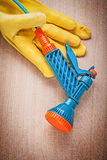 Composition of safety gloves garden hose nozzle on wooden board. Gardening concept royalty free stock image