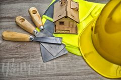 Composition with safety helmet, leather gloves, tools. And decorative house,High dynamic range tone royalty free stock image