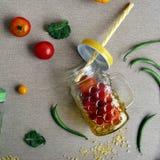 Composition saisonnière décorative des haricots de tomate et d'asperge, des tasses fraîches et des tubes de cocktail photographie stock