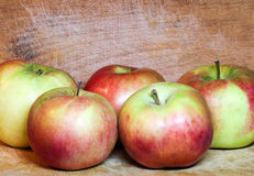 Composition of sappy juicy red apples. Over grungy domestic wooden board Royalty Free Stock Photography
