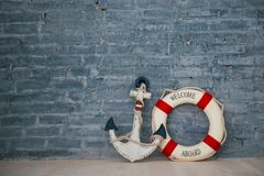 Composition on a sea theme with an anchor and life ring on a gray brick wall. Stock Images
