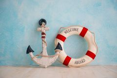 A composition on a sea theme with an anchor and lifebuoy on a blue wall Royalty Free Stock Images