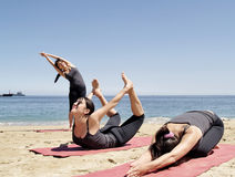 Composition of several bikram yoga poses at beach. Young female yoga teacher practising at beach duplicated three times Royalty Free Stock Images