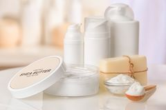 Composition of Shea butter with cosmetic products. On table royalty free stock photo