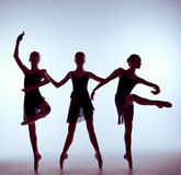 Composition from silhouettes of three young ballet. Composition from silhouettes of three young dancers in ballet poses on a gray background. The outline stock photos