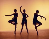 Composition from silhouettes of three young dancers in ballet poses on a orange background. Stock Image