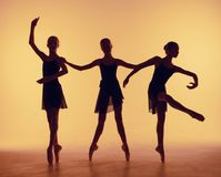 Composition from silhouettes of three young dancers in ballet poses on a orange background. The outline shooting - silhouettes of girls stock photos