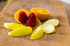 Composition of sliced apples, oranges and strawberries on a wooden surface Royalty Free Stock Images