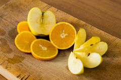Composition of sliced apples and oranges on a wooden surface Stock Image