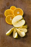 Composition of sliced apples and oranges on a wooden surface Royalty Free Stock Photo