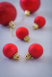 Composition of small and big red christmas balls on gray backgro Royalty Free Stock Photography