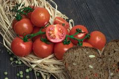 Composition of small red cherry tomatoes on an old wooden table in a rustic style, selective focus.season of vegetables. royalty free stock photo