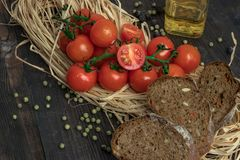 Composition of small red cherry tomatoes on an old wooden table in a rustic style, selective focus.season of vegetables. stock images