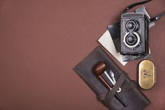 Composition of smoking pipe on a brown leather case, tobacco accessories, old camera and vintage photographs. Top view. Royalty Free Stock Image
