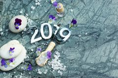 Composition Spa Set With Figures 2019 On Marble With Purple Flowers, Stones And Sea Salt For Bathtubs Royalty Free Stock Images