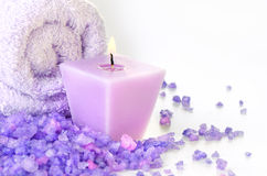 Composition of spa treatment. Candle and Towel with purple sea salt Stock Images