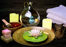 Composition of spa treatment, candles, lotus in bowl with water Royalty Free Stock Photos