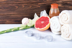 Composition of spa treatment on white wooden background with grapefruit, gladiolus, towels, bath bomb and candles.  With copy spac Royalty Free Stock Photos
