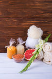 Composition of spa treatment on white wooden background with grapefruit, gladiolus, towels, bath bomb and candles.  With copy spac Stock Images