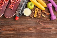 Composition with sport equipment and cereal bars. On wooden background Royalty Free Stock Photo