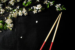Composition with spring flowers and chopsticks on a black background Royalty Free Stock Photography