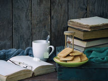 The composition of a stack of old books, open book, tea cups, glasses and plates of sugar cookies on a wooden background. Stock Photos