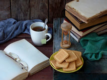 The composition of a stack of old books, open book, tea cups, glasses and plates of sugar cookies on a wooden background. Stock Images