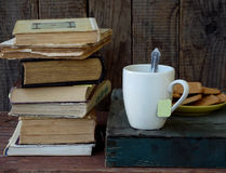 The composition of a stack of old books, tea cups, glasses and plates of sugar cookies on a wooden background. Vintage photo. Side Royalty Free Stock Images