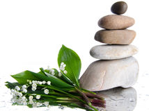 Composition of stacked pebbles with a bouquet of lilies Stock Photo