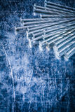 Composition of stainless construction nails on scratched metalli Royalty Free Stock Photography
