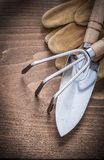 Composition of stainless gardening hand trowel rake leather work Royalty Free Stock Image