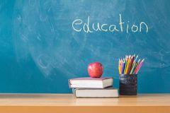 Composition of stationery ,books and an red apple on the desk,The background is blackboard, educational concepts stock photos