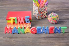 Composition with stationery and phrase \'Time management\' composed from letters on wooden table stock images