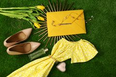 Composition with stylish women`s clothes and accessories for spring on green grass. Flat lay stock photo