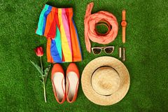 Composition with stylish women`s clothes and accessories for spring on green grass. Flat lay royalty free stock images